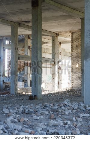 Destroyed buildings. Concrete columns, around the broken bricks and fragments of concrete slabs.
