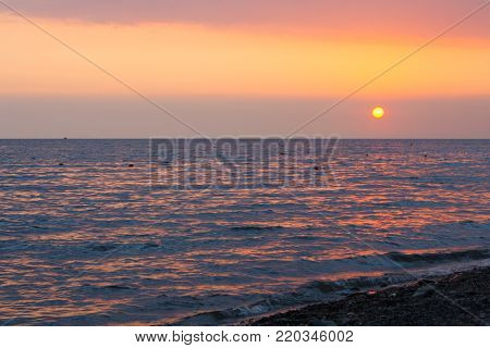 Sunset over the sea. The sun sets over the horizon. The sky over the sea bright red.