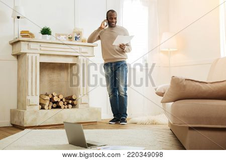 Calling boss. Inspired bearded afro-american man smiling and calling his boss while standing near the fireplace and looking at the sheet of paper and his laptop on the floor