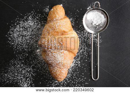 Fresh yummy croissant and sieve with sugar powder on dark background