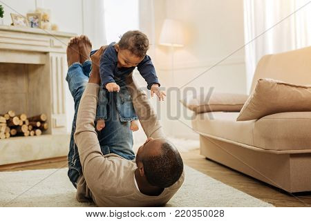 I treasure you. Vigorous dark-haired bearded afro-american man playing with his happy young son while lying on the floor and holding the child in his arms