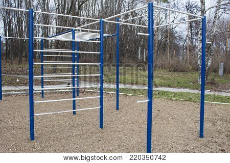 Sports bars in blue and white on the background of park for training in athletics. Outdoor athletic gym equipment. Concept of sport.