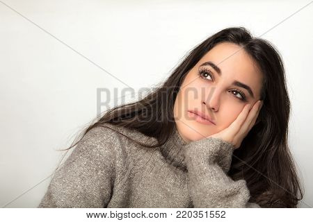 Beautiful woman sitting daydreaming resting her head on her hand staring up to the side with a faraway pensive expression over a white background