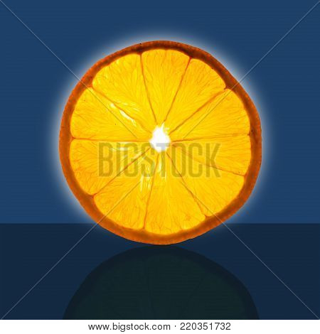 Slice of an orange, baclklit with dark background