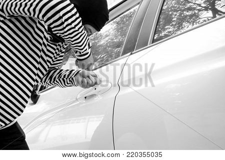 Black and white image of the man robber with a balaclava on his head trying to break into the car/Selective focus/Criminal and car thief concept