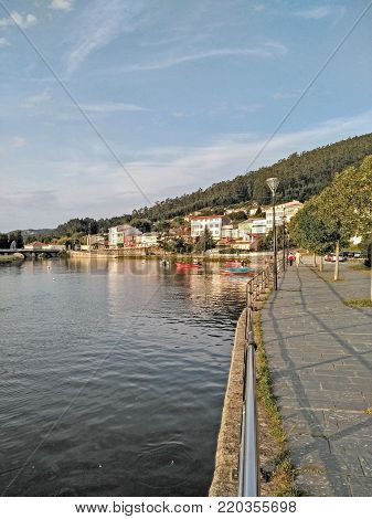 Small fishing village, you can see the bridge that crosses the Xuvia river with some small wooden boats moored to the shore. An area of maritime walk where some people walk on a sunny and quiet day. The village is surrounded by mountains.