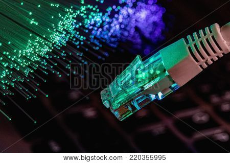 network cable closeup with fiber optical background, color fiber optical background with notebookk, Fiber optics lights abstract background