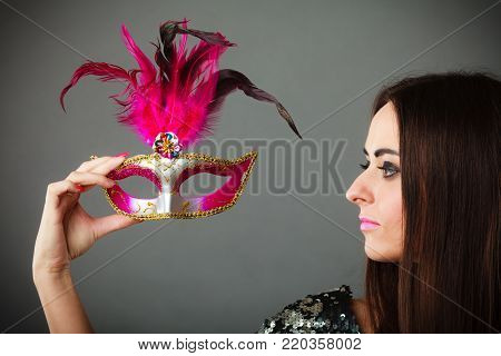 Holidays, people and celebration concept. Closeup woman holding pink carnival venetian mask in hand on gray background.