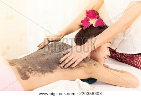 Woman is getting her back scrub by clay in Thai Spa