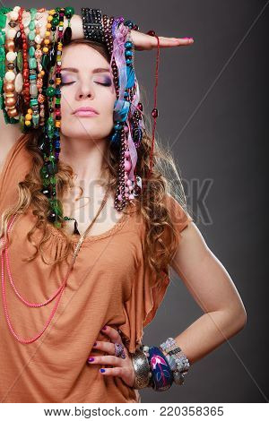 Pretty young woman wearing bracelets holding many plentiful of precious jewelry necklaces beads. Gorgeous fashion girl.
