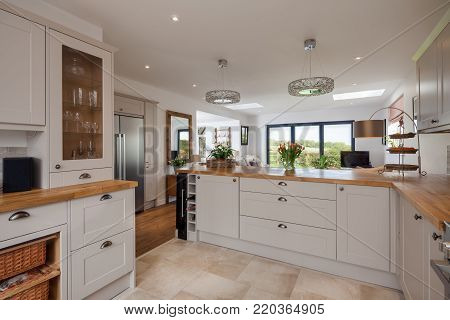 Open plan living family room as viewed from the kitchen area with built in appliances cupboards, drawers, refridgerator and oak countertops