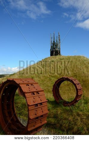 Rusted Machinery components and man made hills form part of an abandoned land restoration plan at Kelty