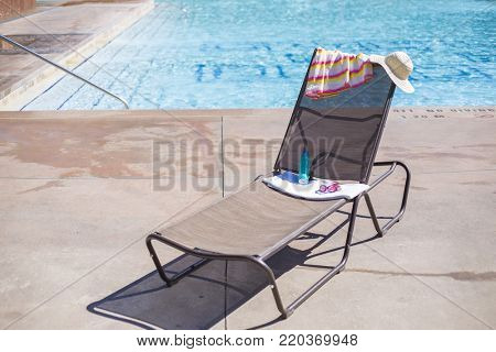 Lounge chair by a swimming pool with sunscreen and a towel. Great generic tropical vacation photo with copy space
