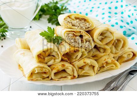 Pancake Breakfast. Pancakes With Meat Stuffing, Served With Sour Cream Sauce On The Kitchen Wooden T