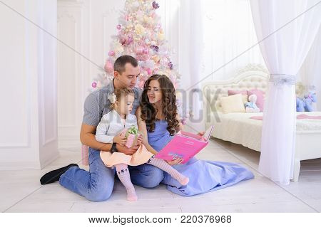 Young happy parents and little daughter to read and consider child's pink book, sitting on floor against backdrop of Christmas ornaments on tree. Dad holding baby girl in  arms, and  mother  reading book.