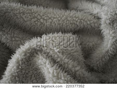 Soft and fuzzy folds are created within this crumpled warm beige blanket
