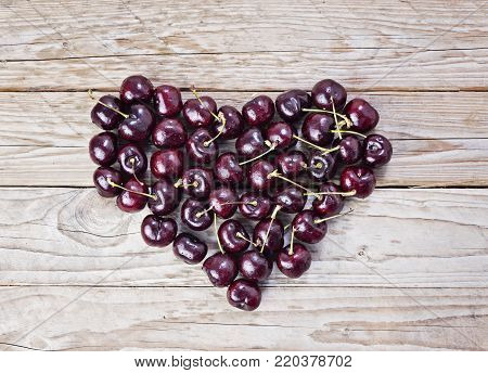 Large Heart of fresh and ripe cherry on wooden background Health care concept Valentine's day