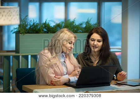 beautiful modern girlfriend girlfriends communicate and work behind laptop in office at dinner table