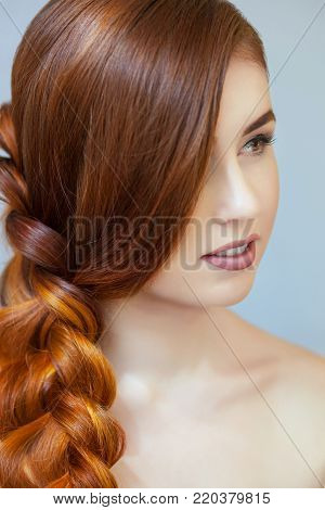 Beautiful Girl With Long Red Hair, Braided With A French Braid, In A Beauty Salon. Professional Hair