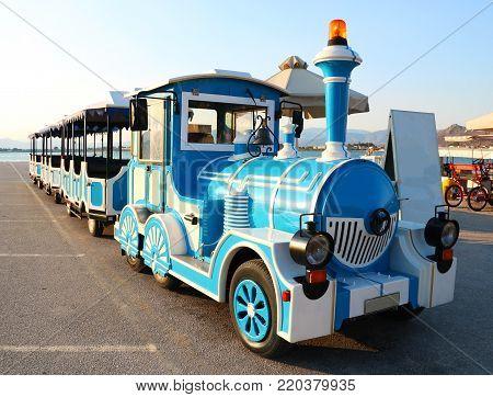 Blue and white tourist excursion locomotive on sea beach in Greece