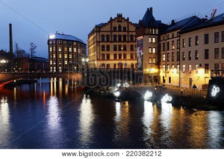 NORRKOPING, SWEDEN - DEC 31, 2017: Nightscape of the beautiful  river Motala Strom and old industrial buildings in central Norrkoping in Sweden, December 31, 2017