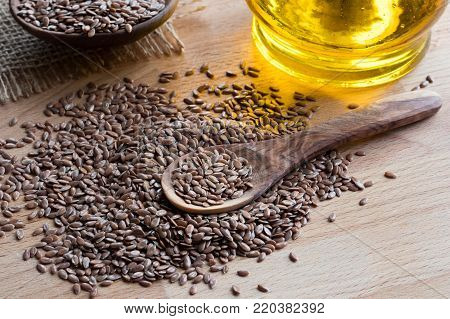 Flaxseed on a wooden spoon, with flaxseed oil in the background