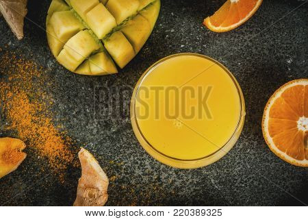 Indian cuisine recipes. Healthy food, detox water. Traditional Indian mango, orange, turmeric and ginger smoothie, on a dark stone table. Copy space top view