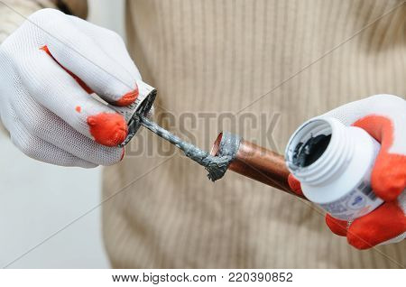 A worker is applying flux to the outside of the copper tube.