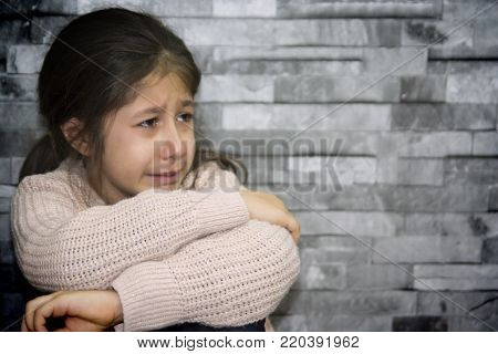 litte sweet girl is crying in front of the wall