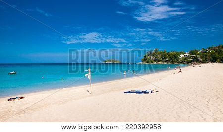 Unidentified people are relaxing on Kata beach during a sunny day in Phuket, Thailand.