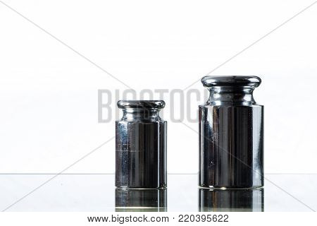 Closeup of two metal weights for calibrating weighing scales, white background