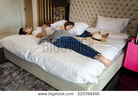 Asian couple traveler tried to travel vacation together and sleep on the white bed.Travel concept.