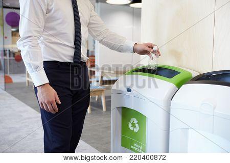 Man in an office throwing plastic bottle into recycling bin