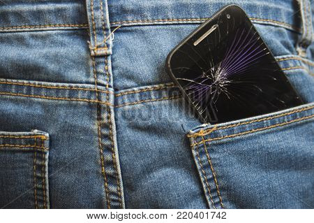 mobile phone broken and cracked touch screen in the back pocket of jeans denim trousers in accident and careless concept