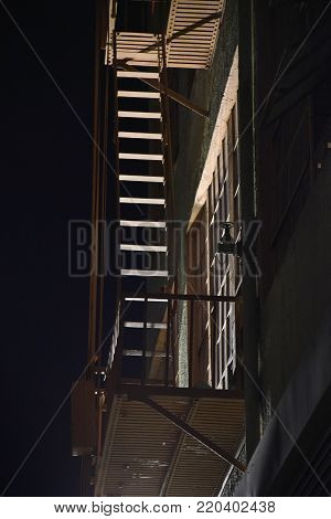 A fire escape on an old building at night