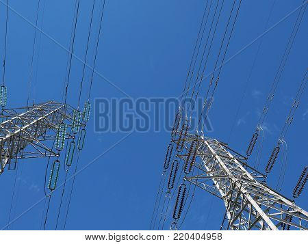 High voltage towers and wires against blue sky in park land, Melbourne Australia 2017