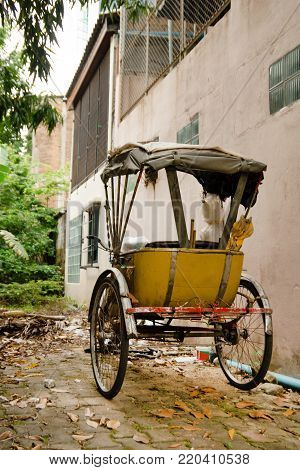 Traditional Thai transport - old yellow trishaw on a street. Chiang Mai, Thailand.
