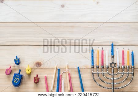 Hanukkah/ Chanukah Jewish holiday background with menorah (Judaism candelabra) burned candles and Dreidel spin game toy with 4 Hebrew letters meaning
