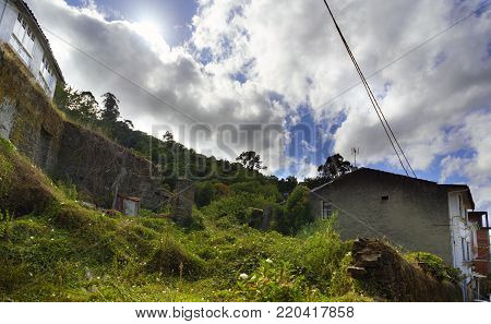 Backlit view of a plot of land with a dilapidated house and a dramatic sky with clouds partially hiding a sun that is seen from the front and a lot of green vegetation in a village called Pontedeume in La Coruna, Spain.