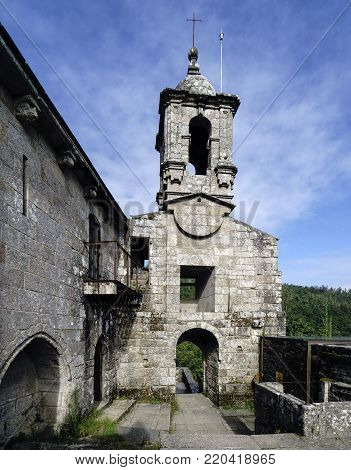 Stone bell tower of the ancient monastery of Caaveiro, dating from the 10th century and which was home to hermits of the area, in Galicia, Spain. In a mountain pass and very green