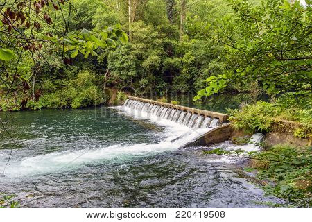 small dam with spillways on the river Eume with shores covered with vegetation in a typical Atlantic oak forest in Galicia, Spain