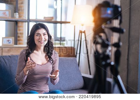 Video blog. Positive delighted joyful woman looking into the camera and telling her story while leading a video blog