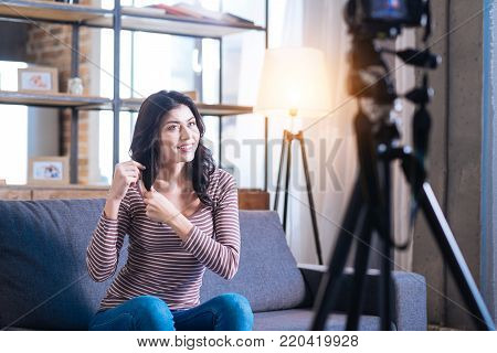 Beauty advice. Joyful positive nice woman sitting in front of the camera and touching her hair while giving some beauty advice