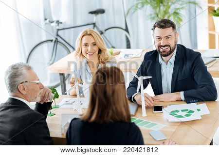Professional employees. Emotional engineers looking glad while sitting together with tiny realistic windmill turbines in front of them and discussing alternative ways of getting energy