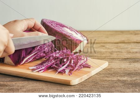 Woman use knife kitchen to chopped or sliced fresh purple cabbage. Shredded cabbage on cutting board on wood table. Prepare vegetable for cooking cabbage salad or coleslaw. Homemade food concept. Sliced red cabbage for cooking.
