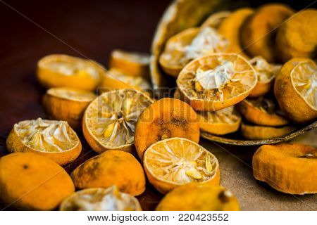 Dried Squeezed Lemons,citrus × Limon In A Rusted Bowl On Wooden Surface.