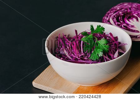 Chopped or sliced fresh purple cabbage in white bowl. Shredded cabbage decorate with coriander put on black granite table. Prepare vegetable for cooking cabbage salad or coleslaw. Homemade food concept of fresh purple cabbage.