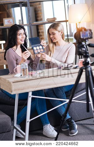 Professional visage. Nice positive young women sitting at the table and looking into the camera while sharing their visage secrets
