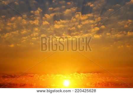 Bright sunrise over the horizon. In the blue sky, small cumulus clouds. Picturesque morning scenery.