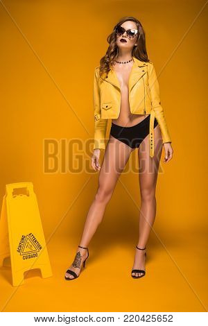 attractive woman in leather jacket and panties standing near wet floor sign
